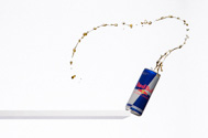 can of Red Bull falling off a shelf with liquid splashing out