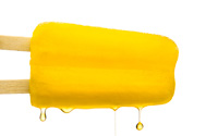 yellow popsicle with liquid dripping